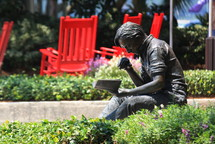 A bronze statue of a man reading a book, red rocking chairs behind him