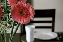 Bouquet of Gerber daisies on a set table.