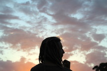 silhouette of a man with dreads at dusk
