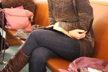 a woman sitting on a church pew reading a Bible next to purses