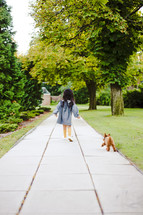 a toddler girl walking a dog on a leash