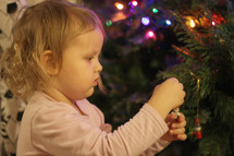 a toddler girl decorating a Christmas tree