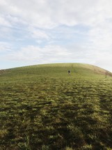 man standing on a green hill
