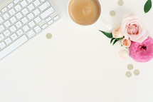 keyboard, coffee mug, glittery dots, and flowers on a desk