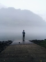 man standing on a dock near a foggy lake