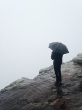 man standing on a rock holding an umbrella