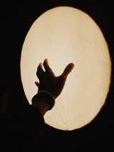 A hand reaching toward an oval light.