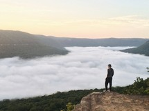 man standing on a mountaintop looking down at a foggy valley below