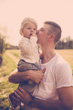 Father holding and kissing child outside.