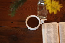 open Bible, flowers in a vase, and coffee mug on a table