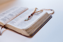 a wooden bead rosary on a Bible