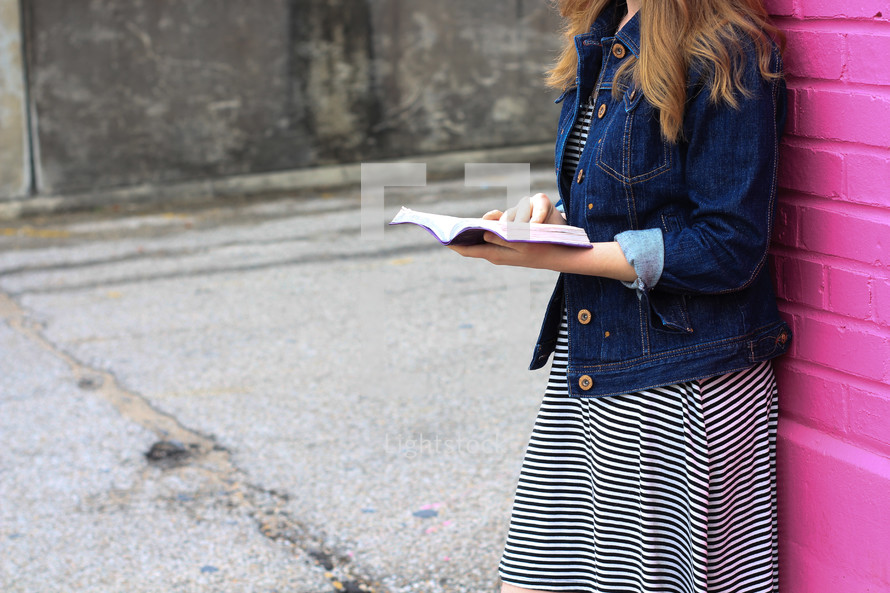 a teen girl in a jean jacket and striped dress reading a Bible in front of a colorful wall