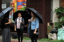 friends chatting holding umbrellas
