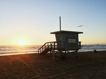 lifeguard stand on a beach at sunset