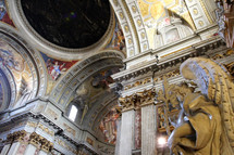 The frescoes and marble covering the dome and ceiling of a basilica in Rome