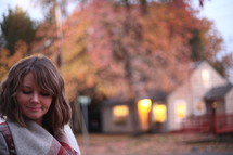 a woman in a coat standing outdoors looking down at the ground in fall