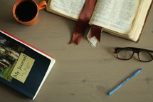 an open Bible, journal, and coffee mug on a coffee table