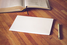 open Bible, envelopes, and pen on a wood floor