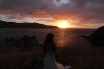 Bride standing outside overlooking the ocean at sunset.