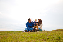 a young family sitting together in the grass