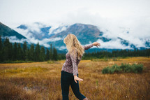 a woman dancing in a valley near a snow capped mountain