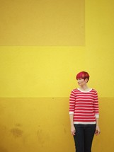 A woman standing in front of a yellow wall.