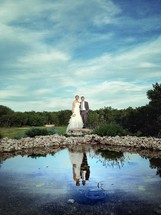 Bride and groom and a pond in the foreground.