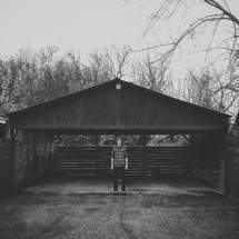 A man standing in front of a covered driveway