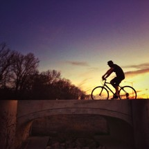 A man riding a bicycle at sunset