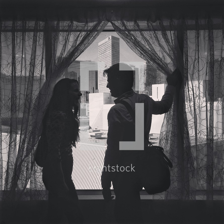 A man and a woman moving the curtains to look out their hotel window.