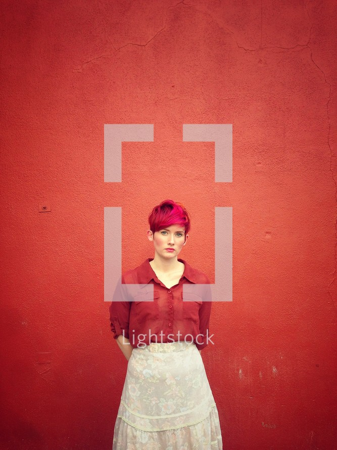 a woman standing in front of a red wall