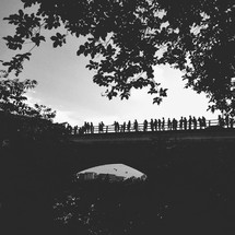 Silhouettes of people standing on a bridge.