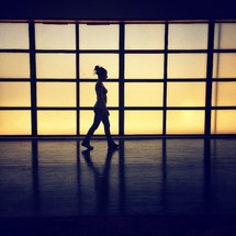 A silhouette of a woman walking in an airport terminal.