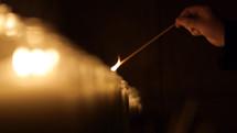 lighting prayer candles in a Catholic church