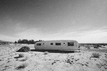 old, abandoned vacation trailer parked out in a desert