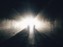 Two people walk through a dark tunnel toward a bright light.