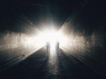 Two people walk through a dark tunnel toward a bright light.