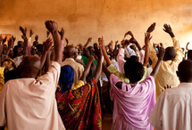 hands raised during a worship service in Africa