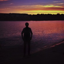 silhouette of a man standing in front of ripples in water at sunset