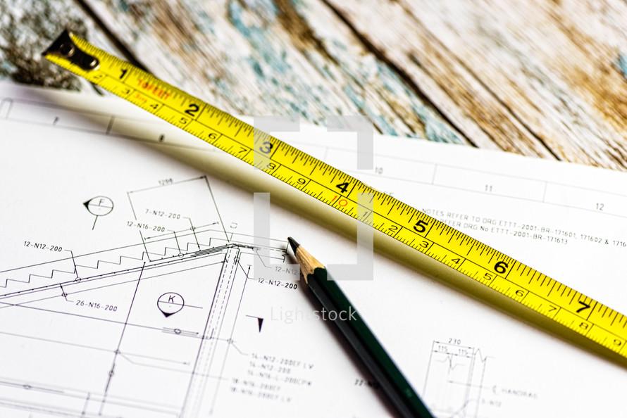 tape measure, blueprints, and pencil