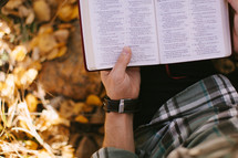 a man sitting in fall leaves reading a Bible