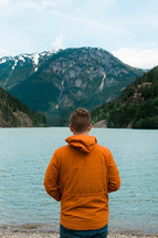 a man in an orange jacket standing by a mountain lake