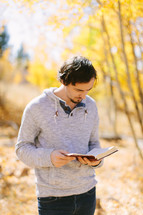 man standing outdoors reading a Bible on a fall day