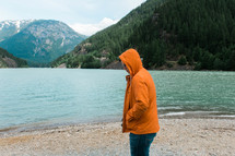 a man in an orange jacket standing on a lake shore