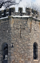 cross on a stone fortress wall