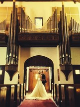 a bride and groom standing under organ pipes in a church
