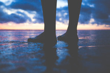 a man's feet standing on wet sand on a beach