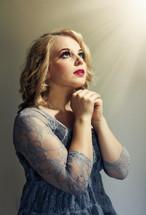 woman in prayer under heavenly light