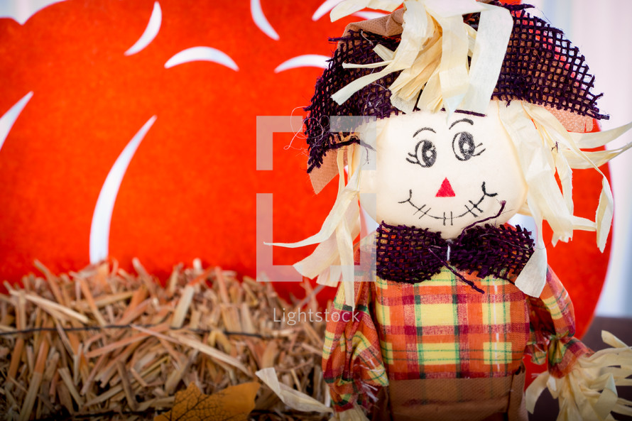 a scarecrow and hay fall decorations