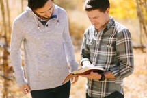 men reading and discussing scripture outdoors on a fall day